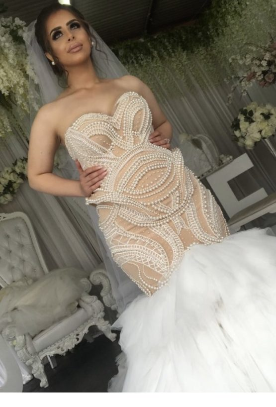 Fitted plus size wedding dress made with pearls in nude color from Darius Bridal